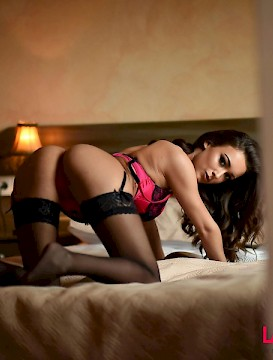Beautiful brunette Lauren Louise doing a striptease on the bed
