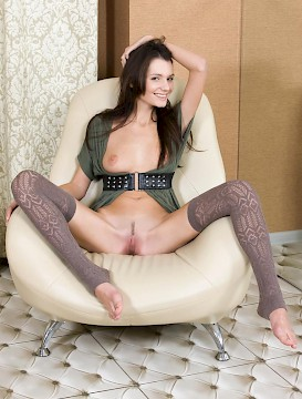 Brunette teen Leila strips and poses on a chair